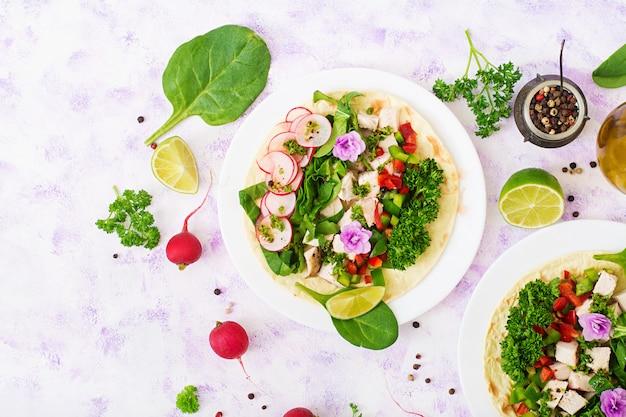 Saludables tacos mexicanos de maíz con pechuga de pollo hervida, espinacas, rábano y pimentón