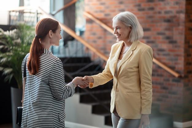 Saludar a un compañero de trabajo. feliz joven empresaria saludando a su colega senior de pie frente a ella en el pasillo
