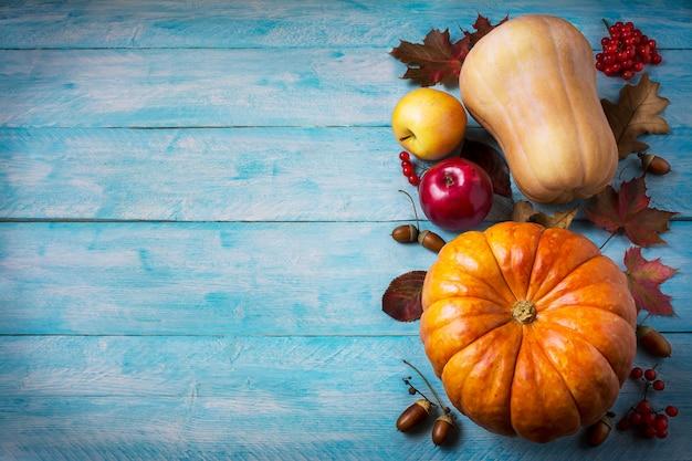 Saludo de acción de gracias con calabazas y hojas de otoño sobre fondo azul.