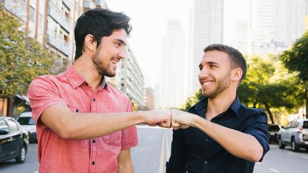 Saludo feliz pareja gay en la calle