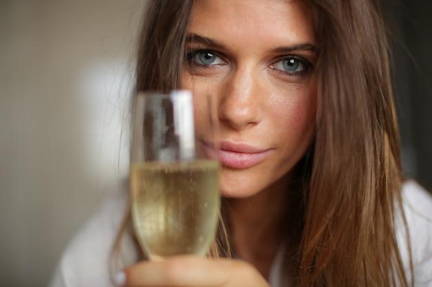 Saludos al amor! una hermosa niña de ojos azules sostuvo una copa de vino a la cámara.
