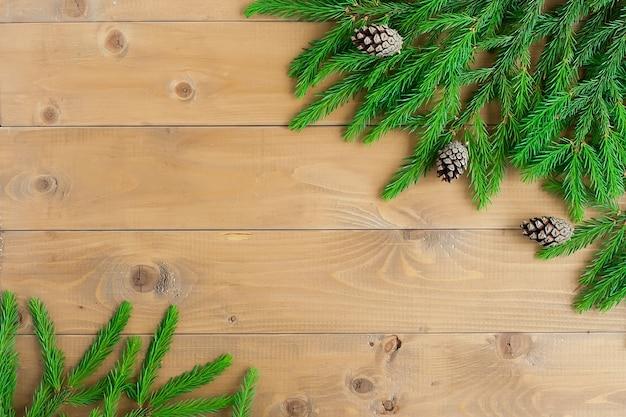 Saludos de año nuevo. las ramas de abeto están dispuestas sobre un fondo marrón