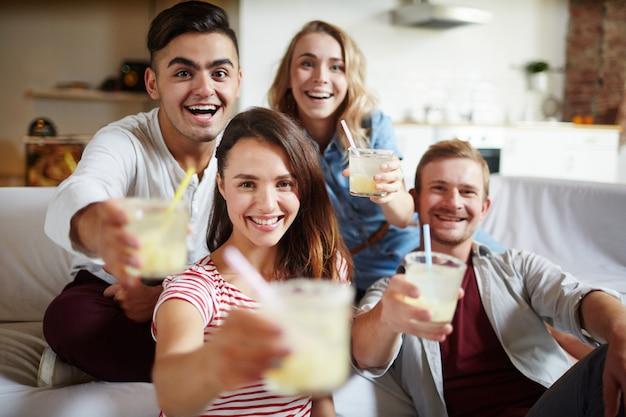 Saludos con bebidas, grupo de amigos.