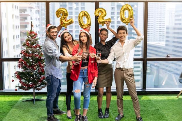 Saludos grupo de personas los mejores amigos vista de ángulo bajo de jóvenes alegres que animan con flautas de champán