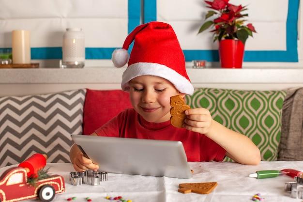 Saludos de navidad en línea de un niño con un gorro de papá noel usando una tableta