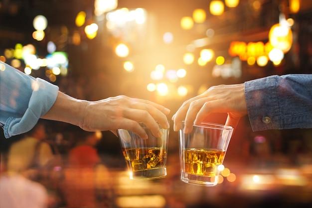 Saludos tintineo de amigos con whisky bourbon bebida en la noche de fiesta después del trabajo en colorido