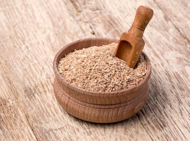 Salvado de trigo en un tazón pequeño de madera