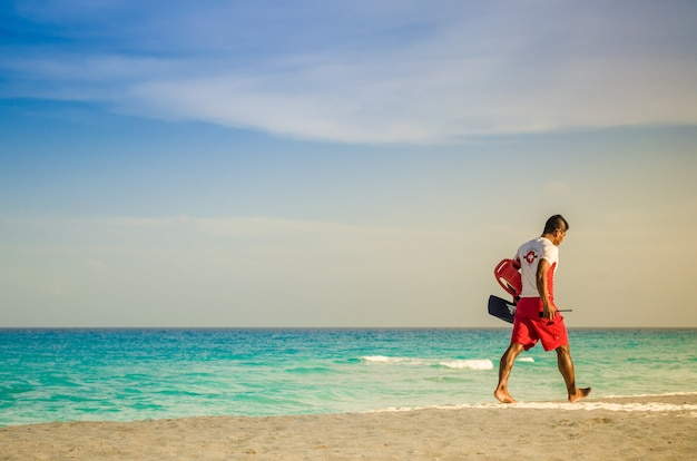 Salvavidas caminando por la playa en cancún.