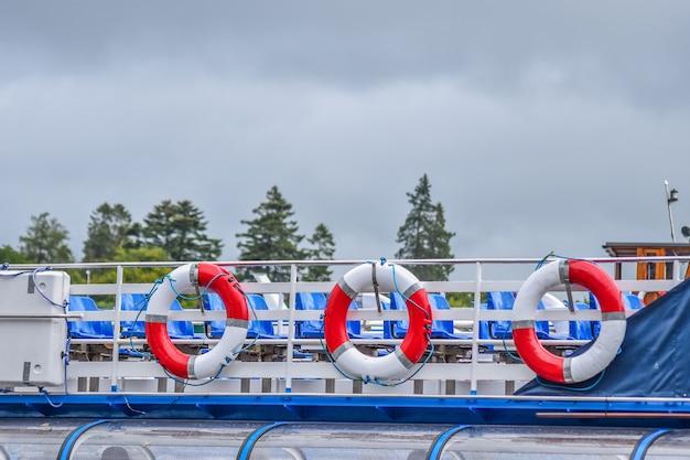 Salvavidas rojos y blancos en el barco con el fondo nublado después de llover,