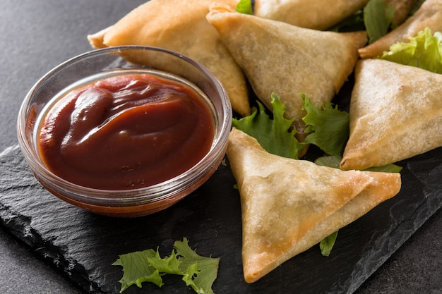 Samsa o samosas con carne y verduras en negro. comida tradicional india. de cerca