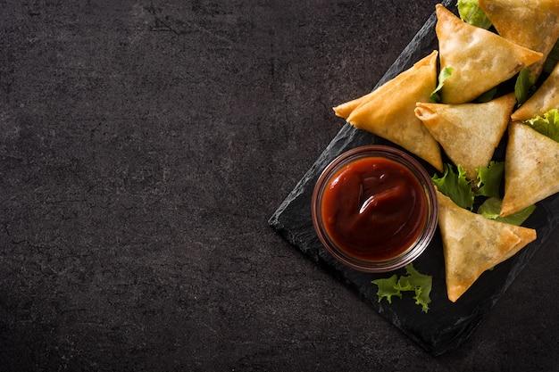 Samsa o samosas con carne y verduras en negro. comida tradicional india copie el espacio