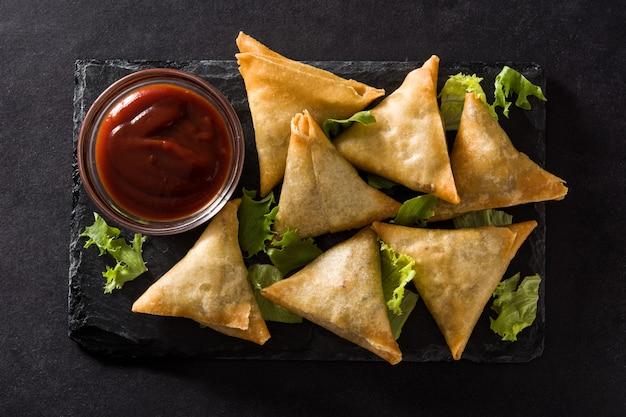 Samsa o samosas con carne y verduras en negro. comida tradicional india.