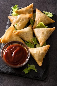 Samsa o samosas con carne y verduras sobre fondo negro. comida tradicional india.