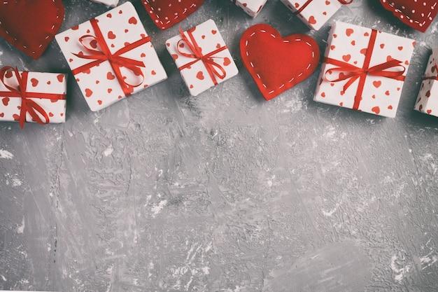 San valentín u otro regalo hecho a mano en papel con corazones rojos y caja de regalo en envoltorio navideño. presente caja de regalo en la vista superior de la mesa de cemento gris con espacio de copia, espacio vacío para el diseño