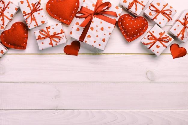 San valentín u otro regalo hecho a mano en papel con corazones rojos y caja de regalo en envoltorio navideño. presente caja de regalo en la vista superior de la mesa de madera blanca con espacio de copia, espacio vacío para el diseño