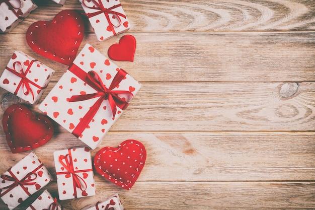 San valentín u otro regalo hecho a mano en papel con corazones rojos y caja de regalo en envoltorio navideño. presente caja de regalo en la vista superior de la mesa de madera naranja con espacio de copia, espacio vacío para el diseño