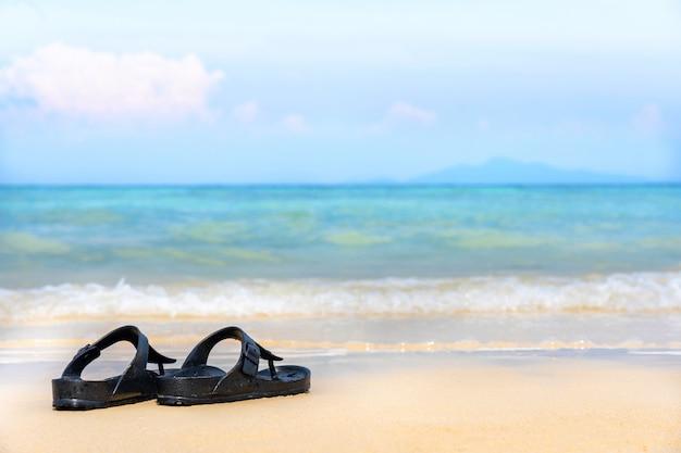 Sandalia flip flop en la playa de arena con mar azul océano