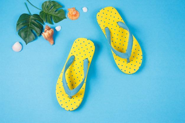Sandalias amarillas sobre fondo de color azul, accesorios de vacaciones de verano.
