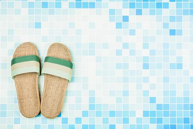 Sandalias en azulejos de cerámica azul en la piscina. - fondo de concepto de vacaciones de verano con copyspace.