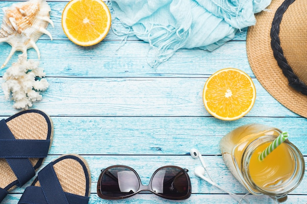 Sandalias azules, sombrero y jugo de naranja sobre fondo azul