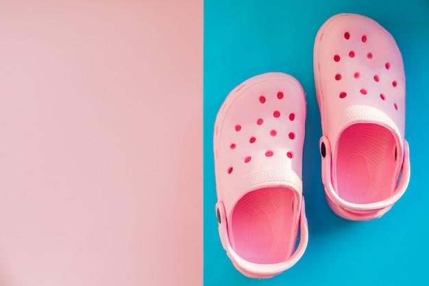 Sandalias de bebé rosa sobre un fondo rosa, rosa azul