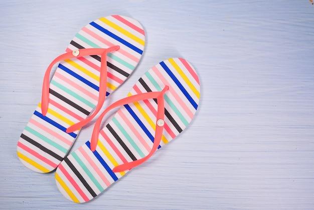 Sandalias de colores sobre fondo blanco de arriba hacia abajo.