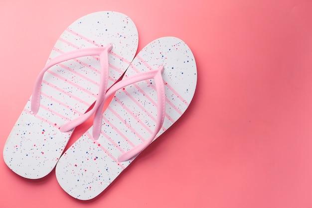 Sandalias de colores sobre fondo rosa de arriba hacia abajo