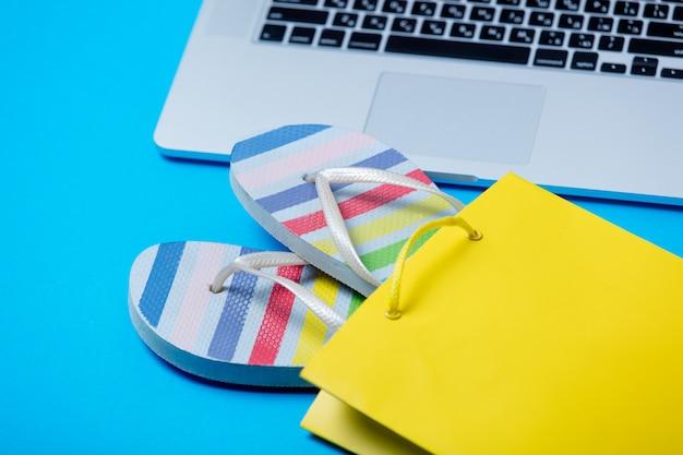 Sandalias coloridas en una bolsa de compras y una computadora portátil fresca en el maravilloso fondo azul