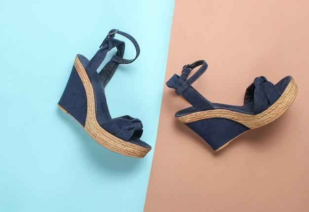 Sandalias femeninas en una plataforma en una mesa de color. zapatos de verano de moda