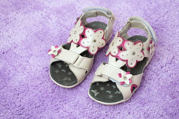 Sandalias para niñas en la alfombra lila