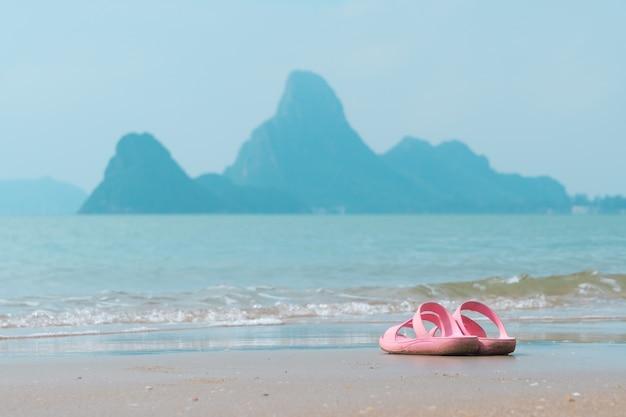 Sandalias rosas en la playa con la montaña en el mar son fondo