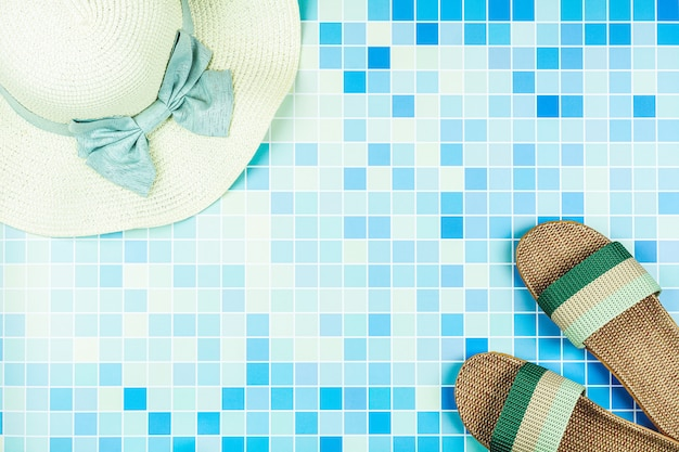 Sandalias y un sombrero de playa en azulejos de cerámica azul en la piscina. - concepto de vacaciones de verano.