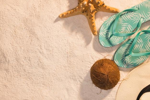 Sandalias tanga de estrellas de mar coco y sombrero sobre arena