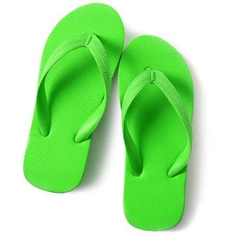 Sandalias verdes brillantes de la chancleta aisladas en el fondo blanco