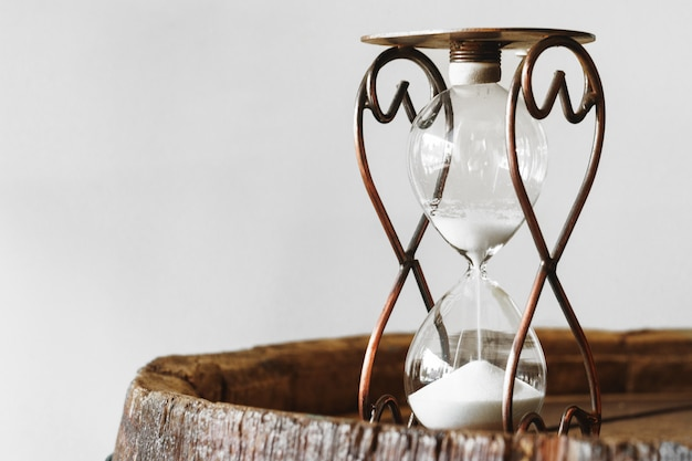 Sandglass en cierre de madera del bakground para arriba. concepto de tiempo