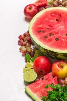 Sandía y diversas frutas sobre fondo blanco.