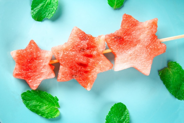 Sandía en forma de estrellas en los pinchos con hojas de menta se encuentra en una placa azul.