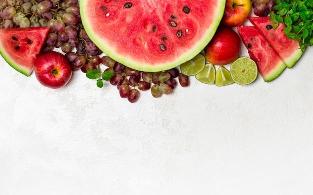 Sandía fresca y frutas sobre fondo blanco.