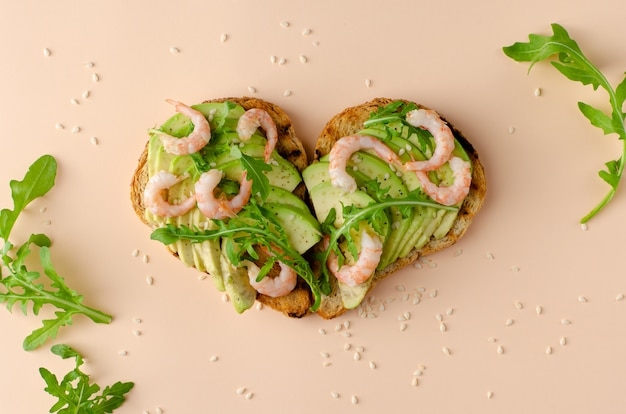 Sandwich abierto con aguacate, gambas y rúcula en forma de corazón