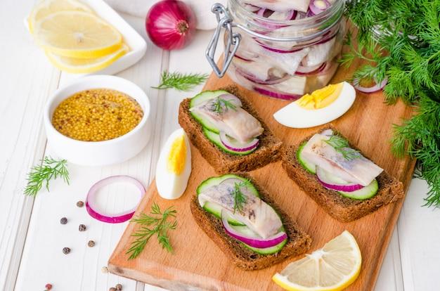 Sandwich abierto con pan de centeno, pepino fresco, cebolla en escabeche, arenque y eneldo sobre madera
