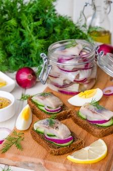 Sándwich abierto con pan de centeno, pepino fresco, cebolla en escabeche, arenque y eneldo sobre una tabla de madera