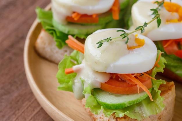 Sándwich abierto con pan tostado y verduras y huevo hervido con aderezo de ensalada.