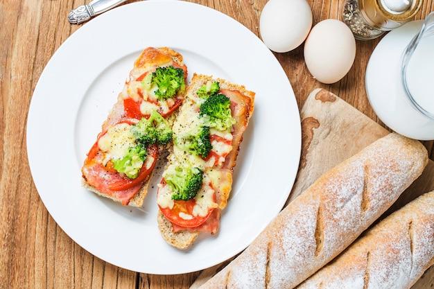 Sándwich abierto con prosciutto, mozzarella y tomates en la mesa de la cocina, enfoque superficial