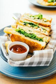 Sándwich con aguacate y carne de pollo con papas fritas.