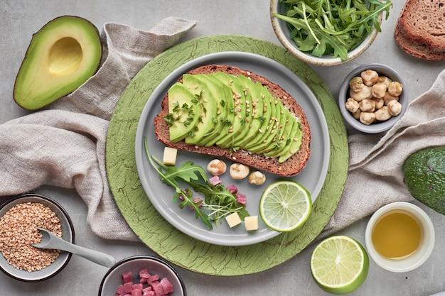 Sandwich de aguacate y ensalada verde con cubitos de jamón sobre textura marrón-verde