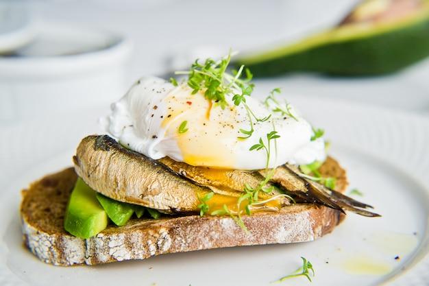Sándwich de aguacate, huevo escalfado y espadín.