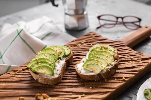 Sándwich de aguacate en pan de centeno oscuro hecho con aguacates frescos en rodajas del concepto de desayuno anterior