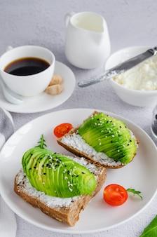 Sandwich de aguacate en pan tostado de centeno oscuro hecho con aguacate fresco en rodajas, queso crema y semillas en un plato blanco con una taza de café sobre un fondo claro.