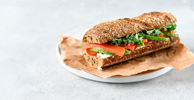 Sándwich con aguacate, salmón, queso crema, tomate y hojas de lechuga