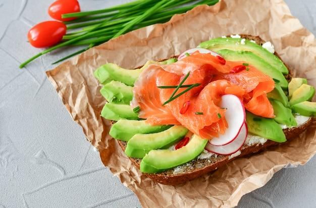 Sandwich con aguacate y salmón sobre un fondo claro